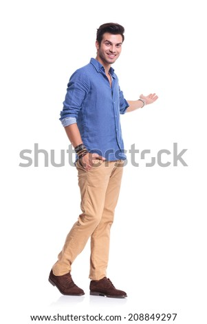 happy casual man presenting something on white background, full body picture - stock photo