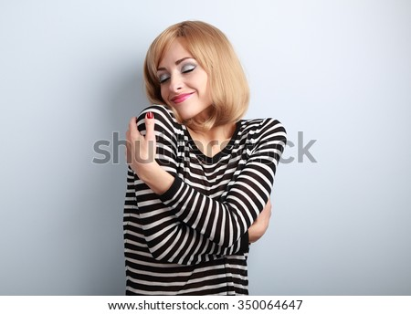 Happy casual woman hugging herself with natural emotional on enjoying face with close eyes. Love concept by yourself - stock photo