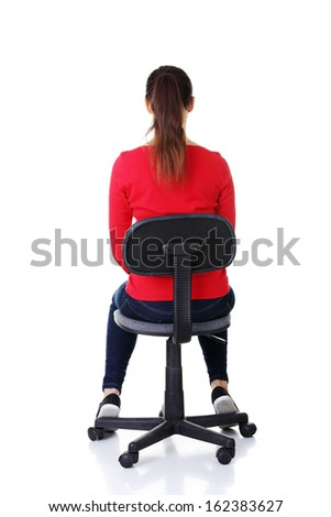 Happy casual woman sitting on a chair. Back view. Isolated on white.  - stock photo
