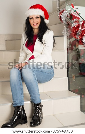 Happy casual woman with Santa hat posing  on stairs home - stock photo