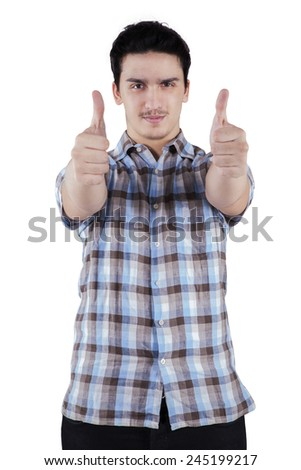 Happy casual young man showing thumb up and smiling, isolated on white background - stock photo
