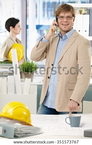 Happy caucasian architect standing with hardhat at office talking on phone. Smiling, looking up, pointing at table. - stock photo