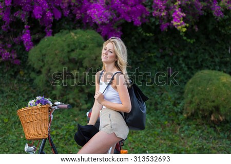 Happy caucasian blonde model enjoying her recreation time riding in the park on her vintage bike with a basket of beautiful flowers, wonderful female relaxing after riding on retro bicycle around town - stock photo