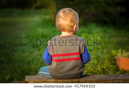 Happy caucasian boy playing outdoor at warm springtime day, boy sitting on bench - stock photo