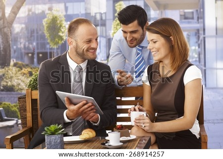 Happy caucasian business team having an outdoor meeting at restaurant using tablet computer. - stock photo