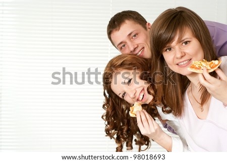 Happy Caucasian campaign of three people eating pizza on a light background - stock photo