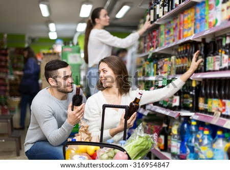Happy caucasian couple choosing alcoholic beverages in a supermarket - stock photo