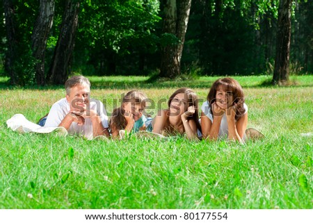 Happy caucasian family lying down on the grass in park - stock photo