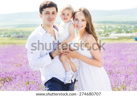 Happy caucasian family mother, father and daughter are wearing white clothes are having fun in lavender field,summer time - stock photo