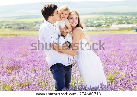 Happy caucasian family mother, father and daughter are wearing white clothes are having fun in lavender field - stock photo