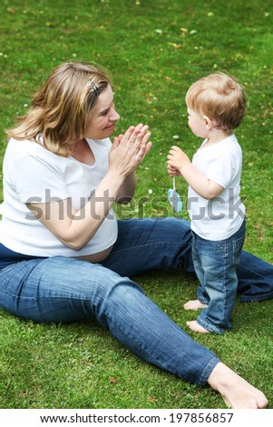 Happy caucasian family of two: little toddler boy and his young pregnant mother having fun outdoors - stock photo
