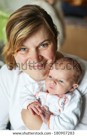 Happy caucasian family of two: newborn baby boy and his happy young mother, indoor - stock photo