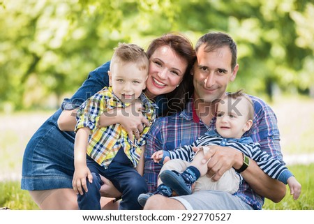 Happy, caucasian family posing outdoors in a summer park.Shallow doff - stock photo