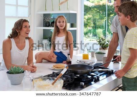 Happy caucasian family standing around stove, son making pancakes on stove - stock photo