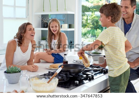 Happy caucasian family standing around stove, son making pancakes on stove - stock photo