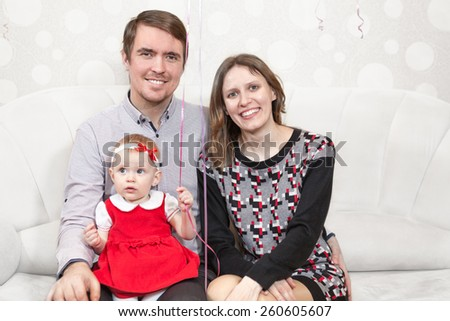 Happy Caucasian family three people sitting together on the couch - stock photo