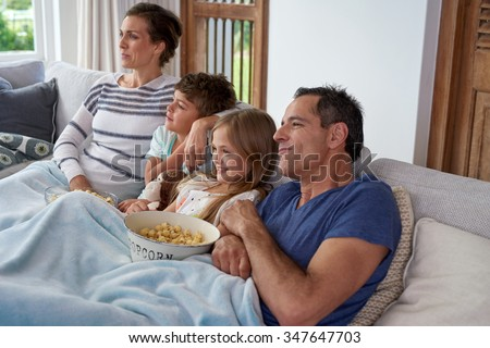 Happy Caucasian family with two children relaxing at home, kids brother and sister watching a movie and having popcorn with parents - stock photo