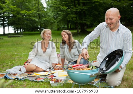 Happy Caucasian friends cooking barbeque meal at an outdoor picnic in forest park - stock photo