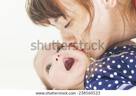 Happy Caucasian Mother Kissing Her Newborn Little Child. Horizontal Image Composition - stock photo