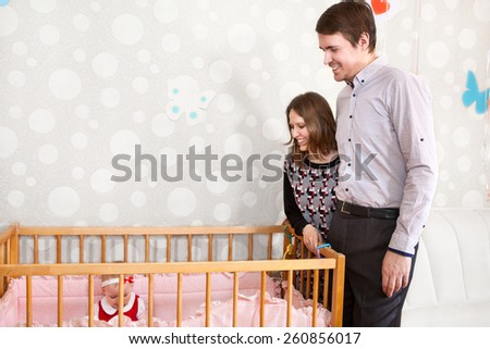 Happy Caucasian parents standing near baby bed and looking at child - stock photo