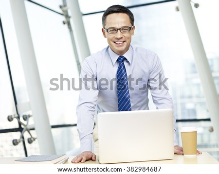 happy caucasian senior corporate executive standing behind desk and laptop computer looking at camera in modern office. - stock photo