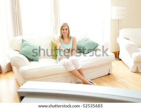 Happy Caucasian woman watching TV sitting on a sofa - stock photo
