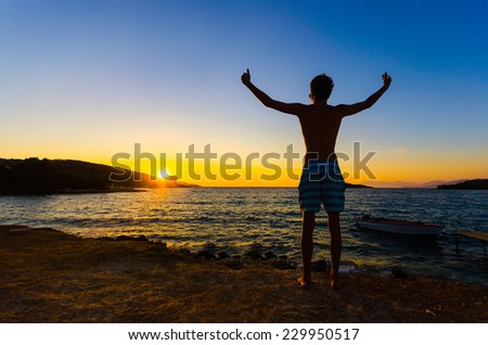 Happy celebrating winning success man at sunset or sunrise standing elated with arms raised up above his head celebrating of having reached summit goal - stock photo