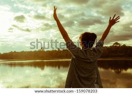 Happy celebrating winning success woman at sunset. - stock photo