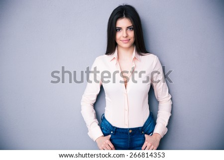 Happy charming woman standing over gray background. Wearing in pink shirt. Looking at camera - stock photo