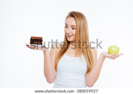 Happy charming young woman standing and holding chocolate cake and green apple over white background - stock photo
