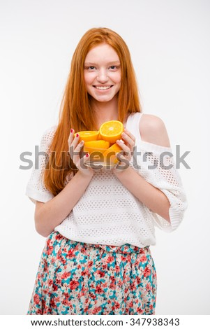Happy cheerful beautiful attractive young redhead female holding oranges in glass bowl - stock photo