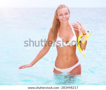 Happy cheerful beautiful girl walking out of the water with snorkeling mask in hands, having fun on the beach, enjoying summer activities - stock photo