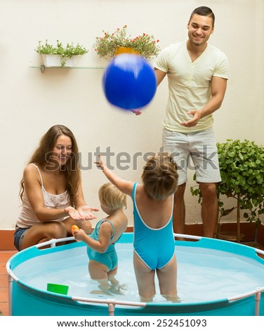 Happy cheerful children and parents playing in pool at terrace. Focus on woman  - stock photo