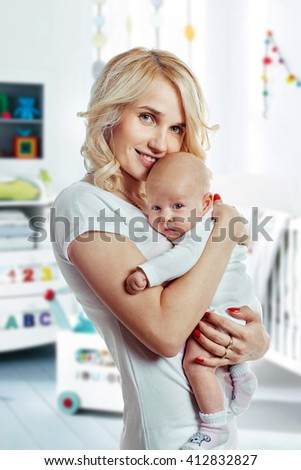 Happy cheerful family. Mother and baby girl laughing and hugging. Closeup tender and love portrait - stock photo