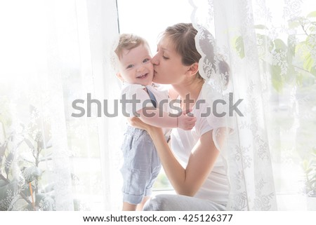 Happy cheerful family. Mother and baby kissing, laughing and hugging. Boy. - stock photo