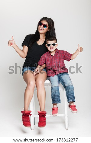 Happy cheerful family, mother and her toddler boy posing in studio wearing sunglasses  - stock photo