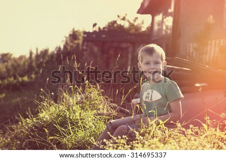 happy cheerful funny little child sitting on grass in countryside on sunset  - stock photo