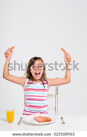 Happy cheerful girl playing with her food, a healthy attitude towards vegetables and fresh produce - stock photo