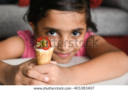 Happy, cheerful, laughing child/ kid/ young girl enjoying her tasty sweet ice cream cone hot on summer vacation/ holiday Kerala, India, Asia. Indian daughter playful holding lollipop and smiling. - stock photo