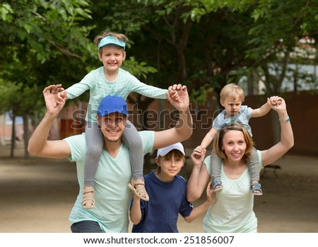Happy cheerful parents with kids staying outdoor and smiling - stock photo