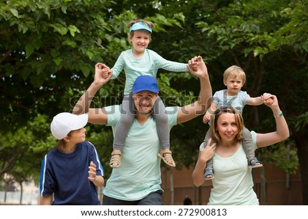 Happy cheerful parents with three children walking outdoor and smiling - stock photo