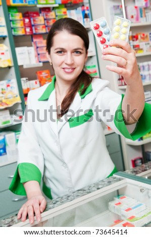 Happy cheerful pharmacist chemist woman standing in pharmacy drugstore with pills - stock photo