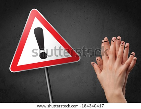 Happy cheerful smiley fingers looking at triangle warning sign with exclamation mark - stock photo