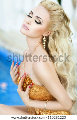 happy cheerful smiling beautiful blond woman closing eyes.alluring lady relaxing and dreaming near pool.Stylish slim girl in sexy golden dress and jewelry - stock photo