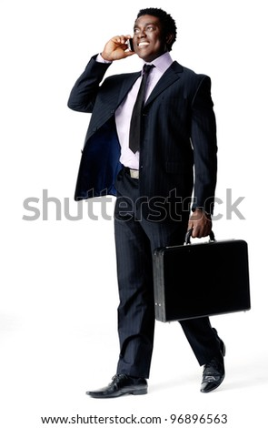Happy cheerful young black businessman walking and talking on his cell phone, isolated on white with a briefcase in hand - stock photo