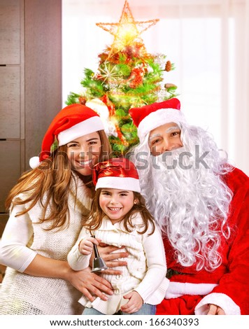 Happy cheerful young family celebrate Christmas holiday at home, little girl with mother and father wearing Santa Claus costume - stock photo