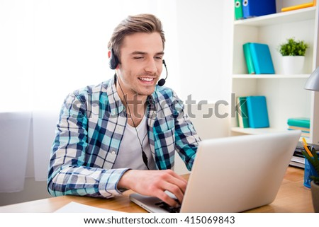 Happy cheerful young worker of call center in head-phones - stock photo