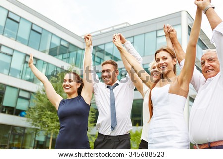 Happy cheering business team holding together the hands up - stock photo