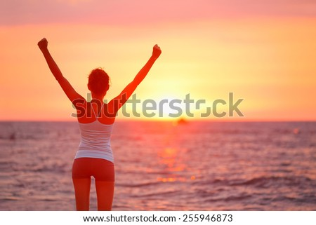 Happy cheering celebrating success woman at beautiful beach sunset. Fitness girl enjoying view with arms raised up towards the sky. Happy free freedom sport concept image outdoors. - stock photo