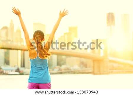 Happy cheering woman in New York City enjoying view and sun on Brooklyn Bridge. Fit female fitness runner joyful and excited after running. - stock photo